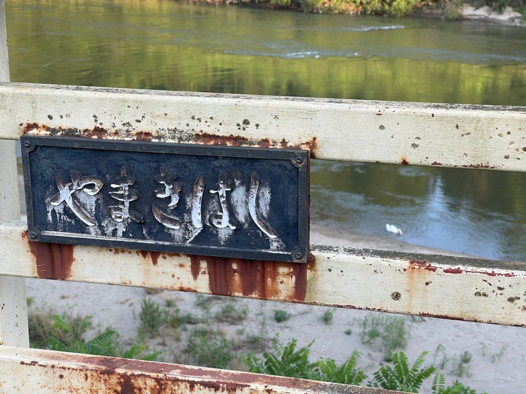 「八巻」の地名の由来は、側の川に八つの「巻」があったたからと言われています。 その「八巻」には「八巻橋」があり、ある時、マイクとバスが停まり、降りてきて記念撮影を始めました。それは一体何者?